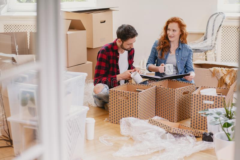 Happy young people packing stuff into boxes while moving out fro. M home concept stock image
