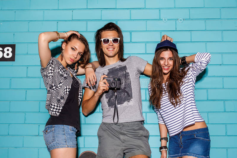 Happy young people with photo camera having fun in front of blue stock image