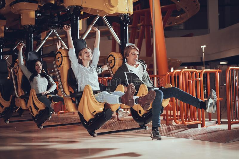 Happy young people ride on attractions. stock photo