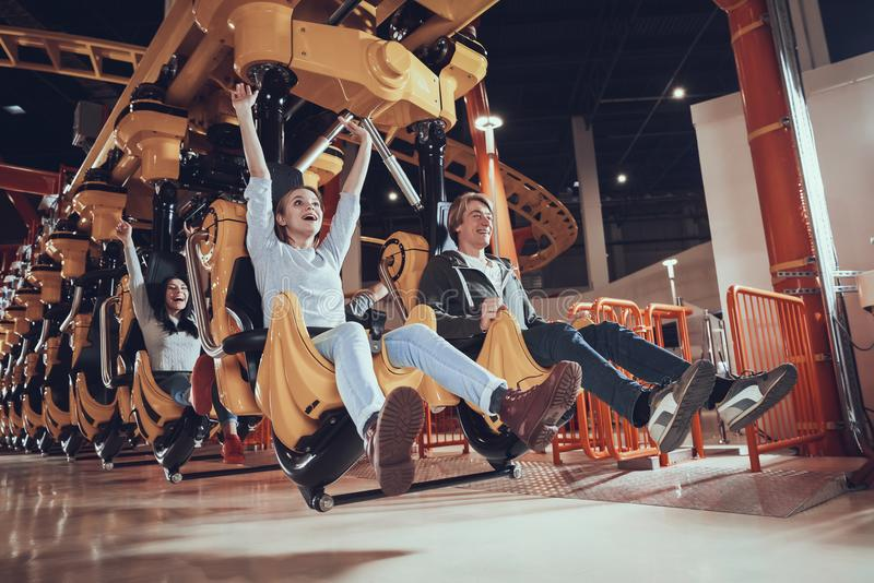 Happy young people ride on attractions. stock images