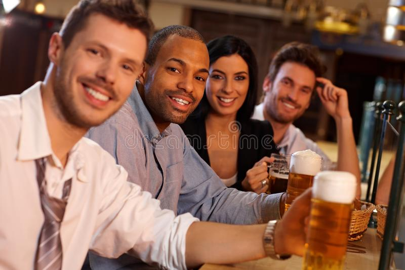Happy young people sitting in pub, drinking beer stock photos