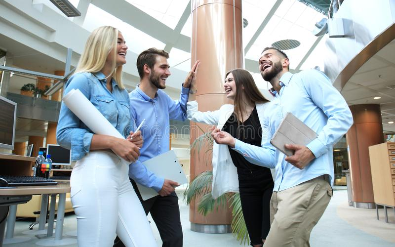 Happy young people standing in office and giving high five to their colleagues. royalty free stock photos