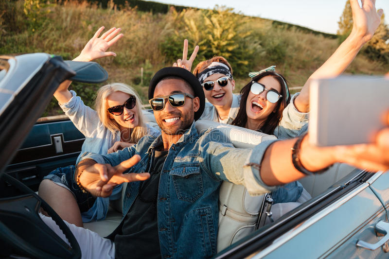 Happy young people taking selfie with smartphone in the car royalty free stock photography
