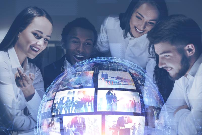 Happy young people watching streaming video. Happy young people looking at futuristic video streaming interface. Concept of hi tech and social media. Toned image royalty free stock photos