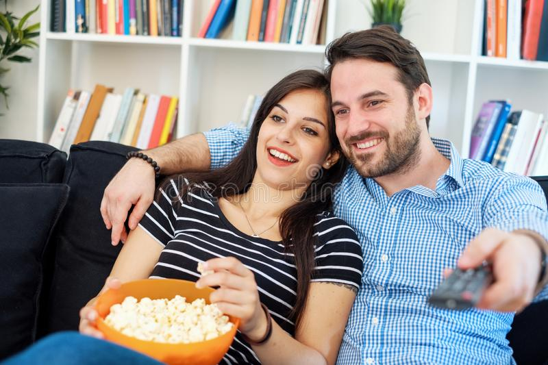 Happy young people watching TV on the couch stock images
