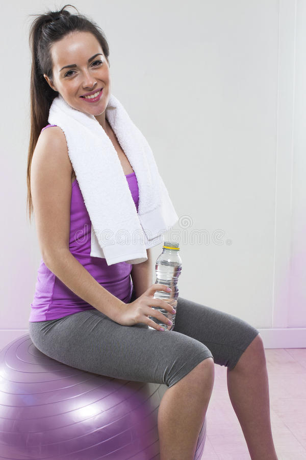 Happy young Pilates girl relaxing with water after the work out royalty free stock photo