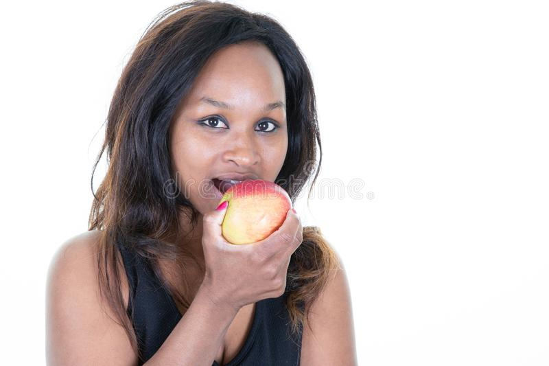 Happy young pregnant african woman holding red apple stock image