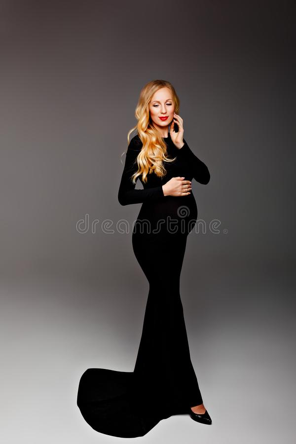 Happy chic young pregnant woman in stylish black dress holding belly bump and posing in light. Stylish fashionable mom, hugging. Happy young pregnant blond woman royalty free stock image