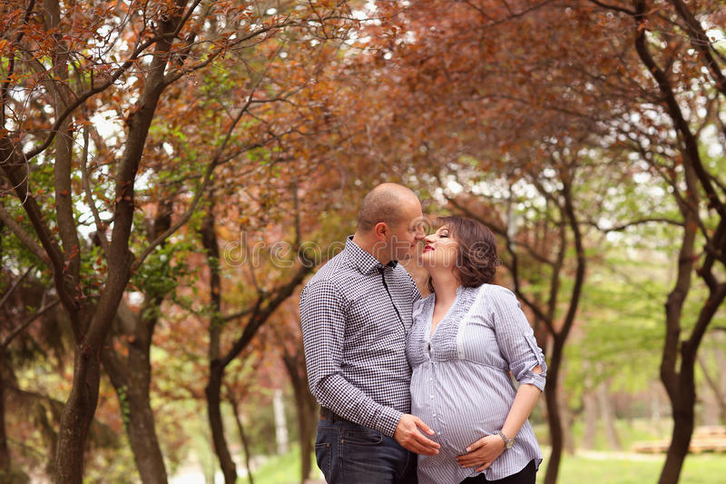 Happy and young pregnant couple embracing in nature royalty free stock photography
