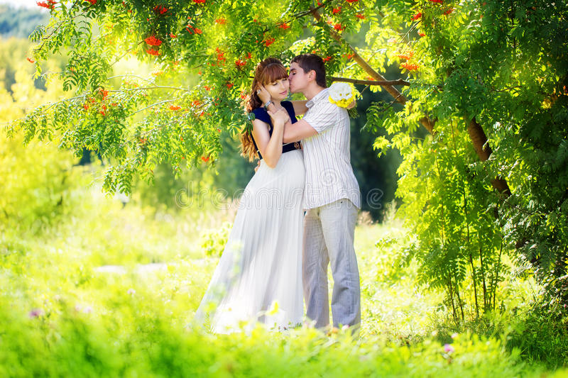 Happy and young pregnant couple hugging in the park. Summer vacation. New life concept. Future mother and father. stock image