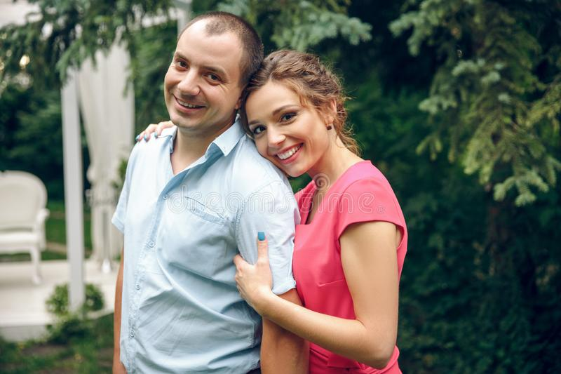 Happy and young pregnant couple in park in summer stock photography