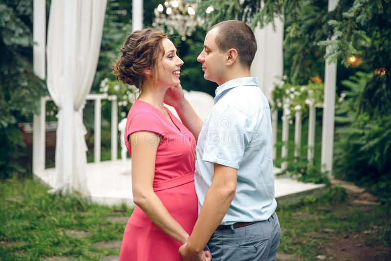 Happy and young pregnant couple in park in summer stock image