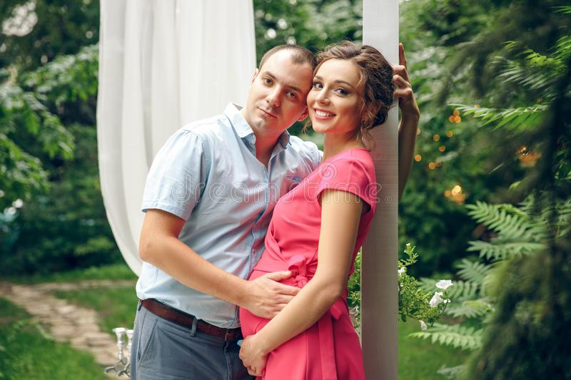 Happy and young pregnant couple in park in summer stock images