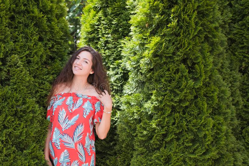 Happy young pregnant girl. on a green background. in a comfortable dress. Portrait of a happy and cheerful pregnant woman royalty free stock photography