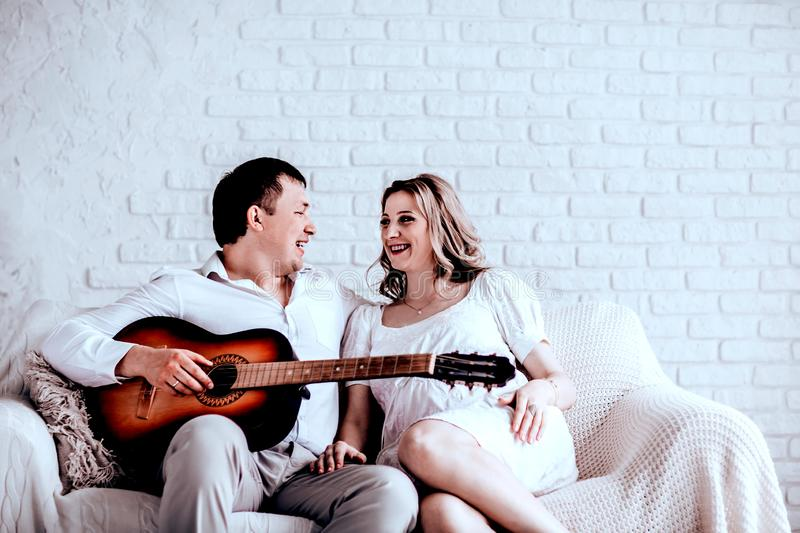 Young pregnant woman and her husband sitting on the couch on a free evening royalty free stock image