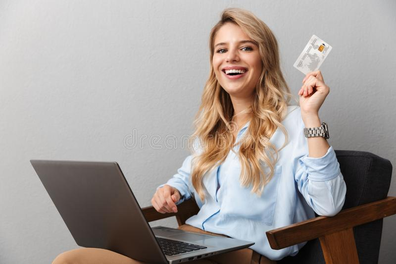 Happy young pretty blonde business woman posing  grey wall background holding credit card using laptop computer. Image of a happy young pretty blonde business royalty free stock images