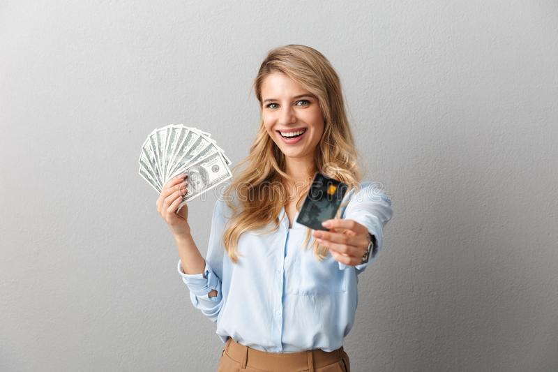 Happy young pretty blonde business woman posing isolated grey wall background holding credit card and money royalty free stock photography