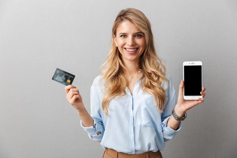 Happy young pretty blonde business woman posing  grey wall background holding credit card showing display of mobile phone stock photography
