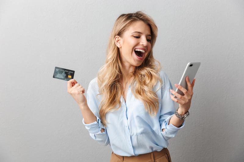 Happy young pretty blonde business woman posing isolated grey wall background holding credit card using mobile phone. Image of a happy young pretty blonde stock images