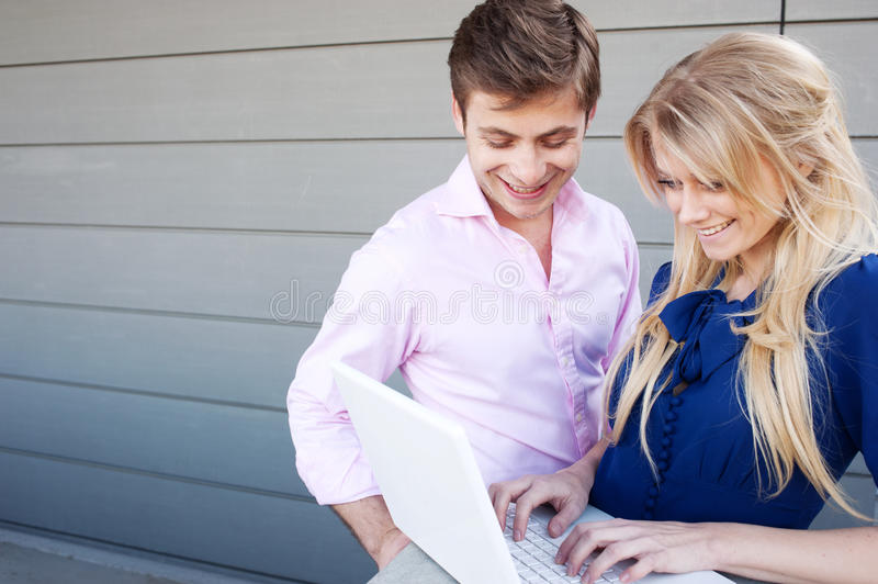 Happy, young professional couple using laptop stock photography