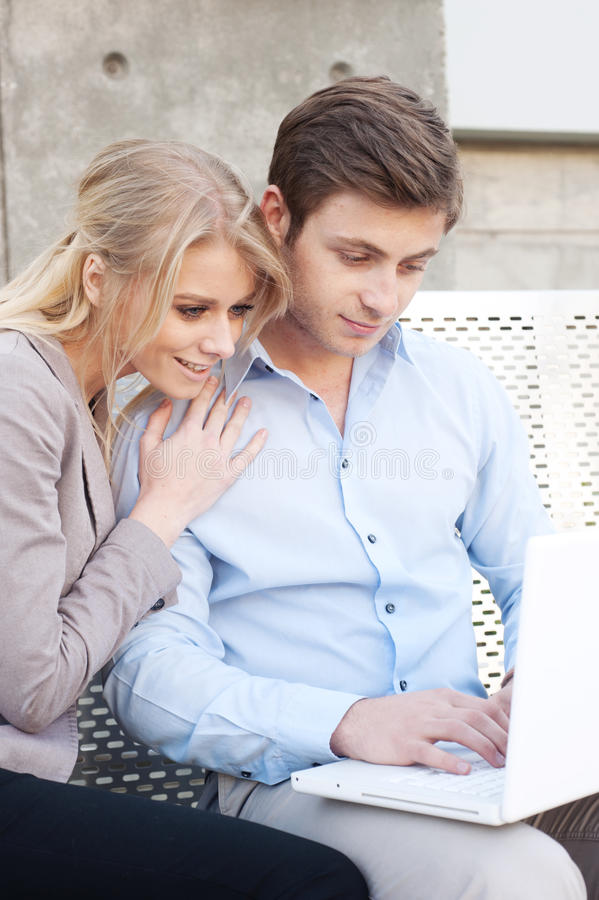 Happy, young professional couple using laptop royalty free stock images