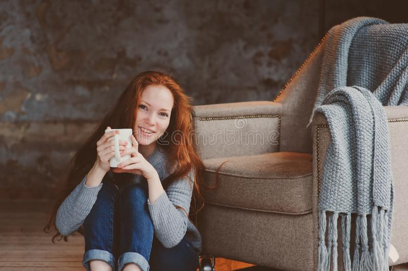 Happy young readhead woman drinking hot coffee or tea at home. Calm and cozy weekend in winter stock photo