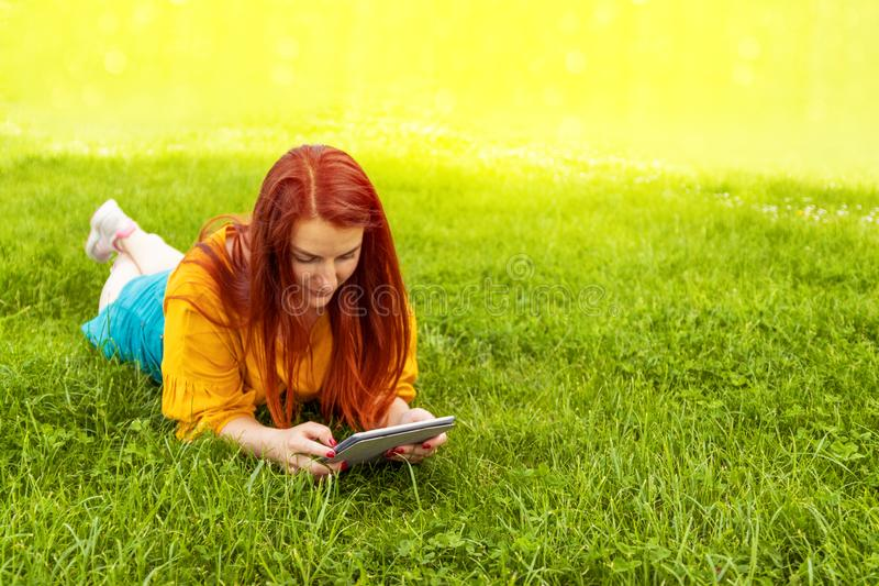 Young red-haired girl in a yellow jacket and green skirt lying on the grass and using a tablet, watching an educational video in a stock images