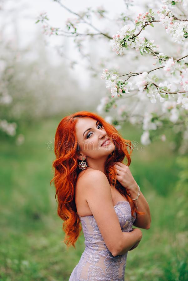 Happy young red-haired woman stands in blossoming apple orchard royalty free stock photography