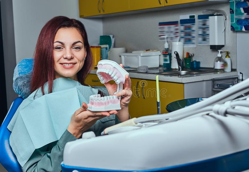 Young redhead woman sitting in a dentist chair and holding the denture in a dentist office. stock photo