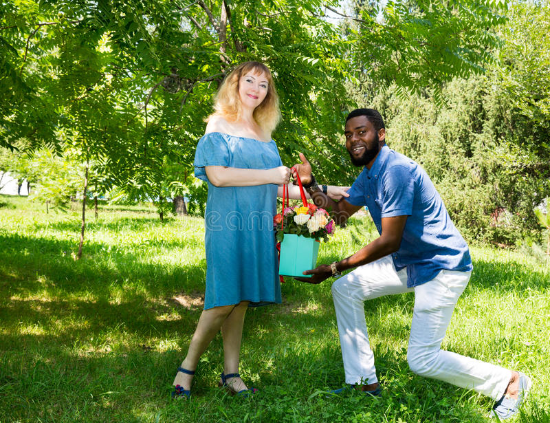 Happy young romantic couple in love. Black man and white woman. Love story and people`s attitudes. Beautiful marriage concept. Happy young romantic couple in stock image