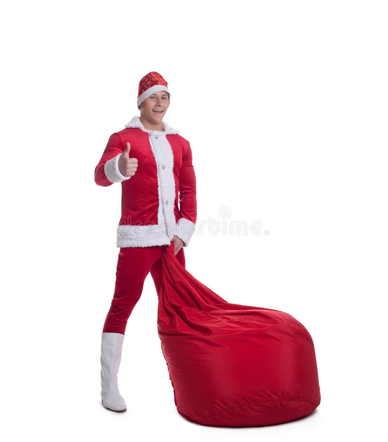 Happy young santa claus with huge red bag. Thumbs up isolated stock photos