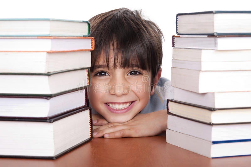 Happy young school boy surrounded by books royalty free stock photography