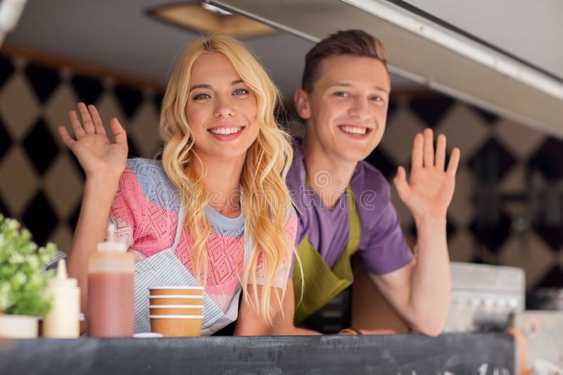 Happy young sellers waving hands at food truck. Street sale and people concept - happy young sellers waving hands and greeting at food truck stock photography