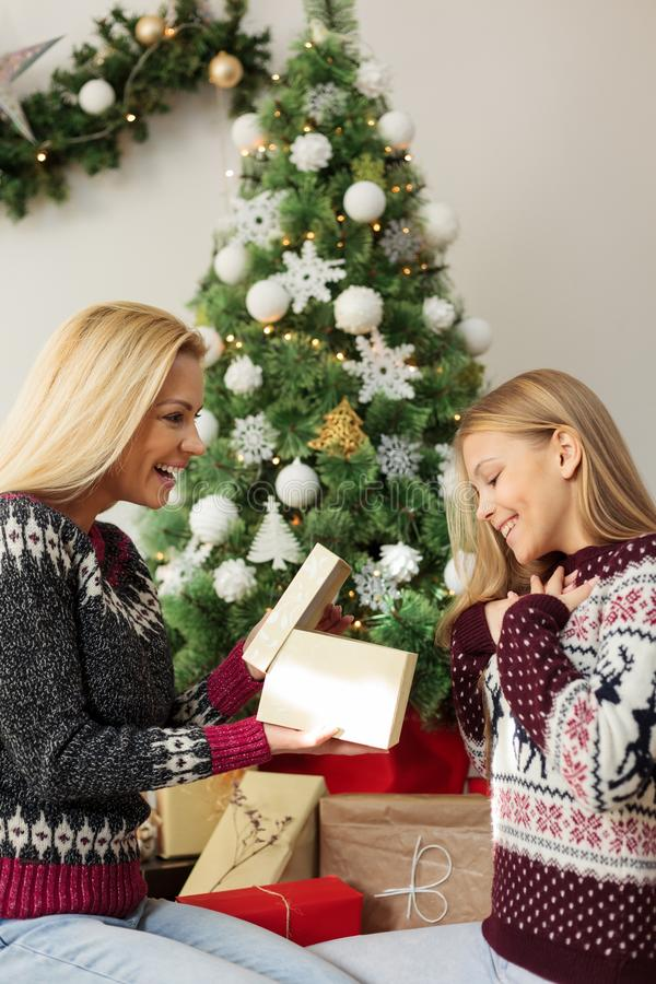 Happy young single mother giving Christmas gift to her beautiful teenage daughter. Single parent family opening gifts on Christmas day. Decorated Christmas stock photography