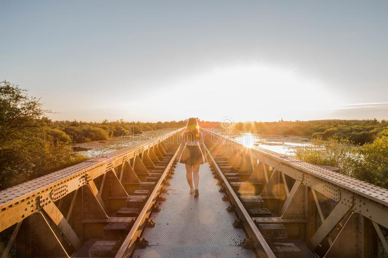 A happy young slender girl walks near a bridge in the rays of the summer sun. stock photo