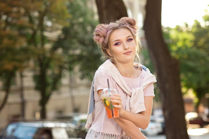 Happy young smile girl in a pink T-shirt and a sweatshirt with a bright make-up and hair bun sitting outside with a stock images
