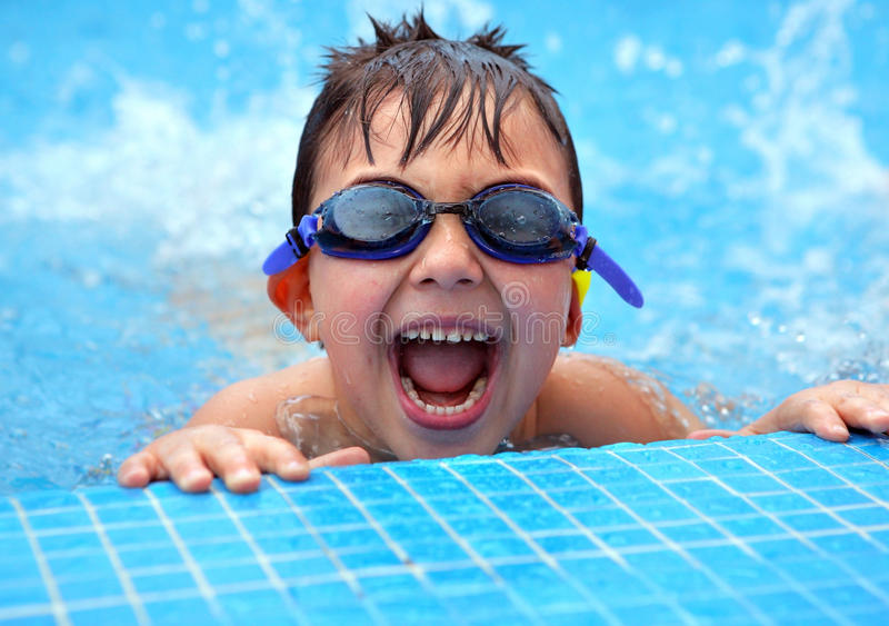 Happy young smiling boy in the swimming pool royalty free stock image