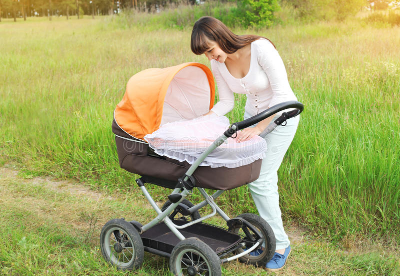 Happy young smiling mother walking with baby stroller outdoors stock images