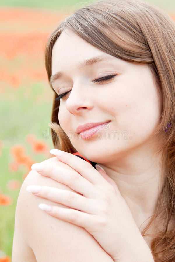 Happy young smiling woman. A young girl is on the field of poppies on a sunny summer day. She hugging herself. She has a healthy facial skin and hand with long royalty free stock photos