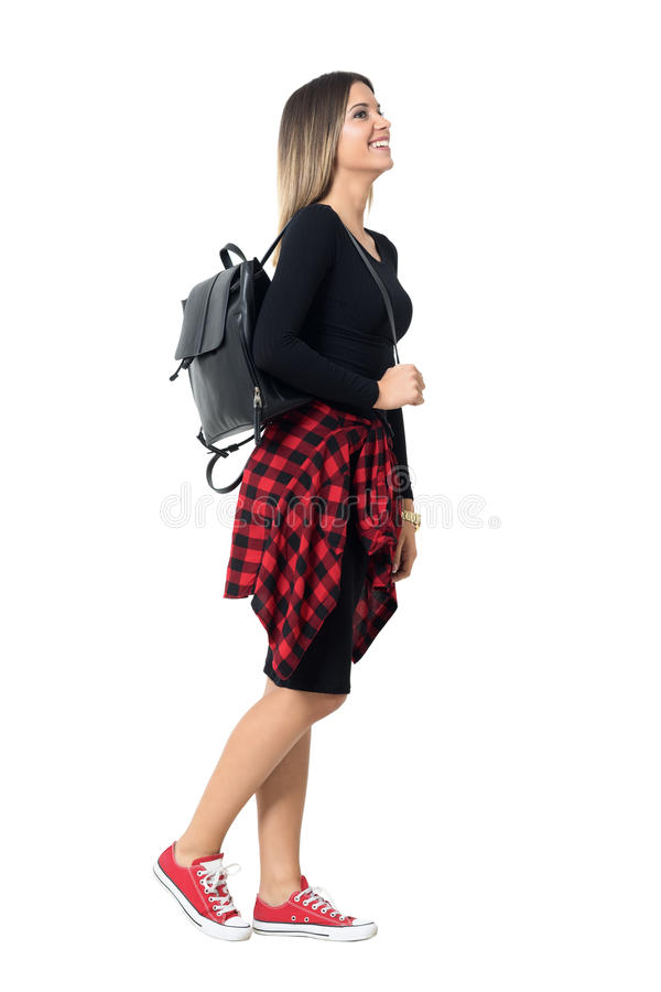 Happy young street style woman in sneakers and red dress walking side view. stock photo