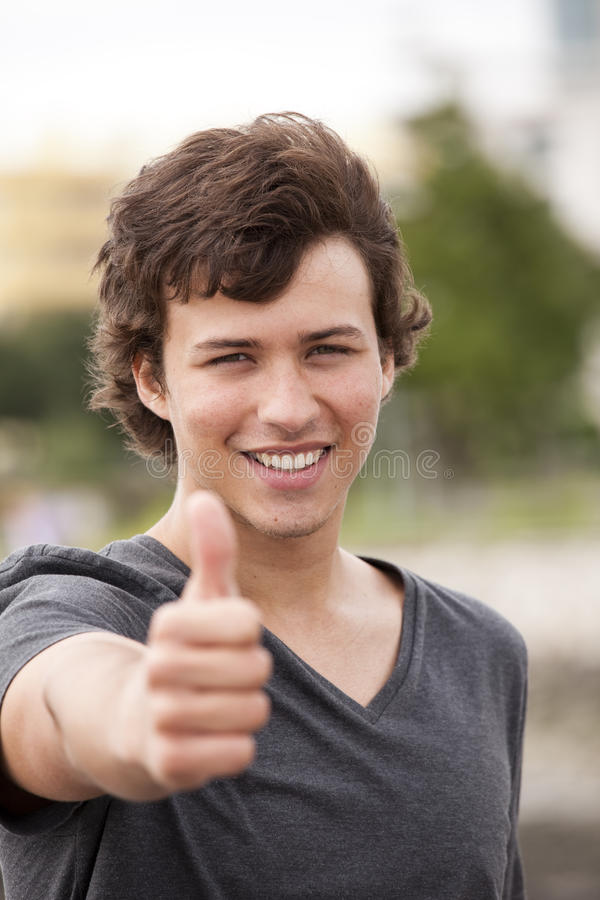 Happy young student. Young man smiling and gesturing OK royalty free stock photos
