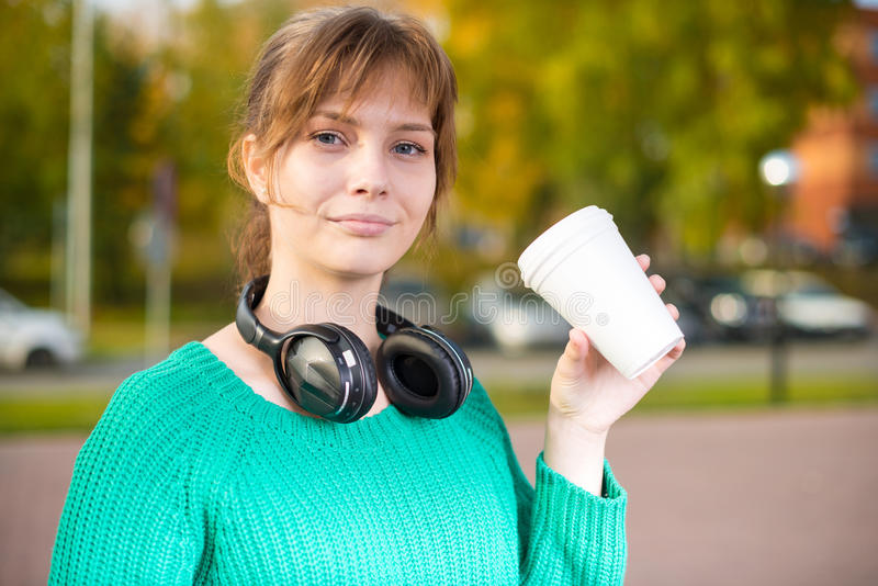Happy young student girl drinking take away coffee royalty free stock photography