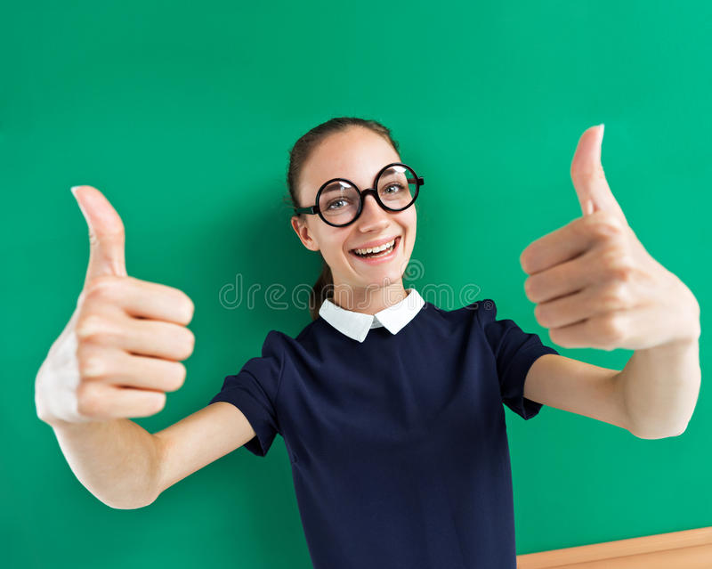 Happy young student showing her thumbs up. royalty free stock images