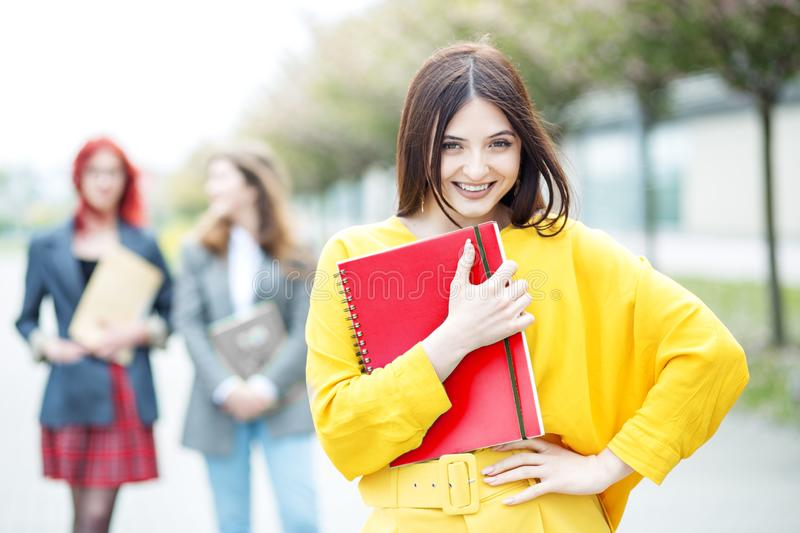 Happy young student standing with a folder. Education concept, exams, friendship and group of people royalty free stock image