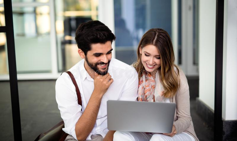 Happy young students studying and learning with a laptop royalty free stock photography