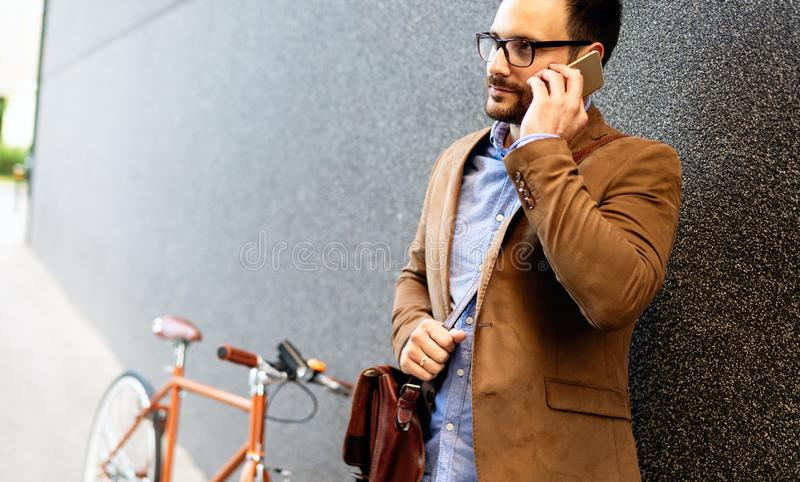 Happy young stylish businessman going to work by bike. Young stylish businessman going to work by bike in the city royalty free stock photography