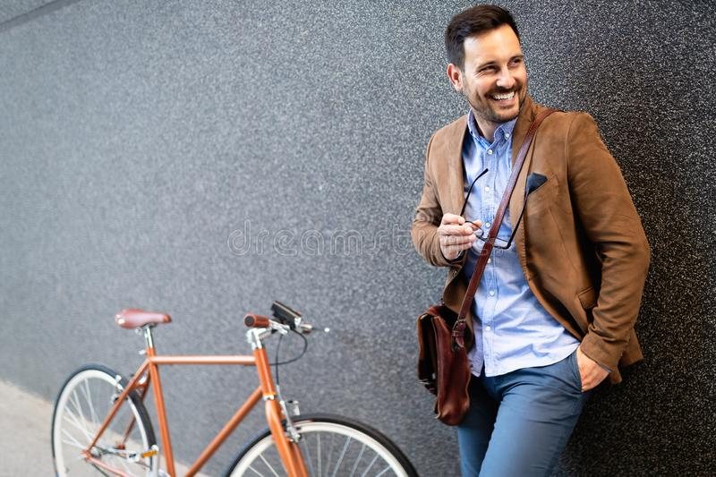 Happy young stylish businessman going to work by bike stock photography