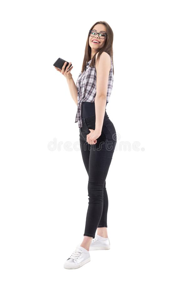 Happy young stylish millennial teenage woman smiling and posing holding mobile phone in hand royalty free stock photography