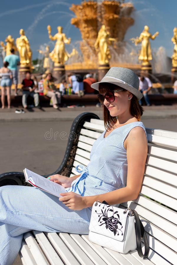 Happy young and stylish woman with hat and book sitting on the bench in the park. royalty free stock photography