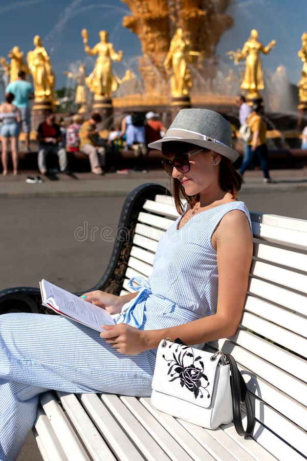 Happy young and stylish woman with hat and book sitting on the bench in the park. stock photos